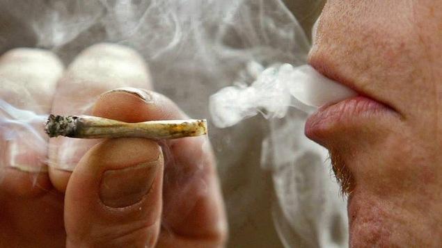 Un homme tient un joint, et vient de prendre une bouffée de marijuana, et de la fumée sort de sa bouche.