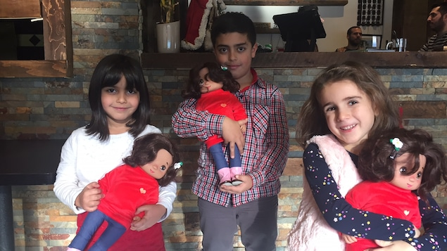 Deux fillettes et un garçon tenant dans leur bras une poupée Shaam, aux cheveux et aux yeux bruns.