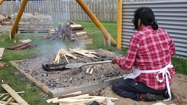 Une femme innue prépare la banique dans le sable et la cendre.