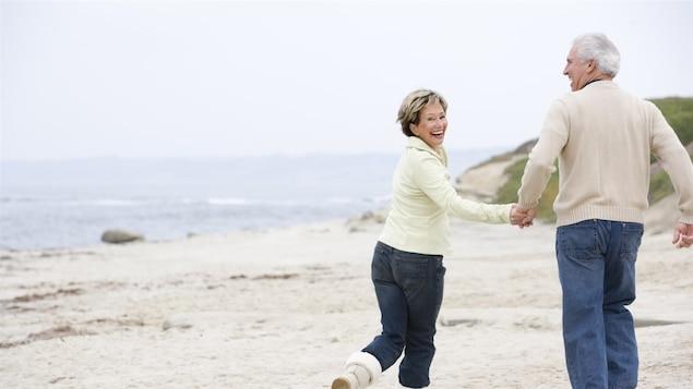 Un couple de retraités se promène gaiement sur la plage.