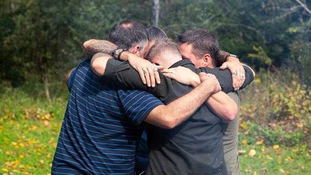 Sébastien Goulette, Dominique Brière, Frédérick Lavergne et Érick Moyneur se prennent dans leur bras, en forêt, à leur retour de Bosnie.