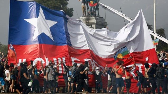 Des manifestations devant un immense drapeau chilien.