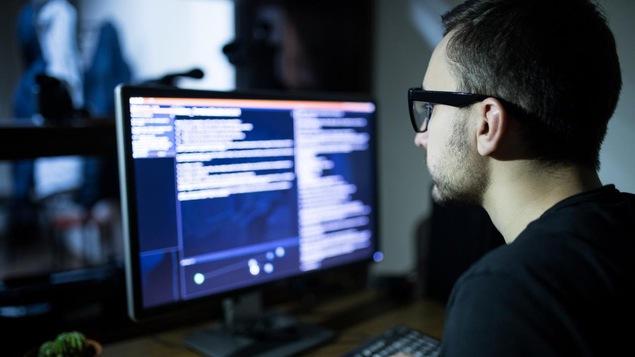 Un homme portant des lunettes utilise un ordinateur.