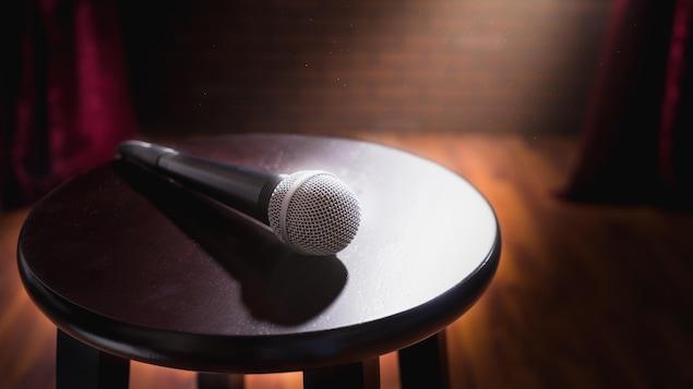 Un micro déposé sur un tabouret sur une scène.