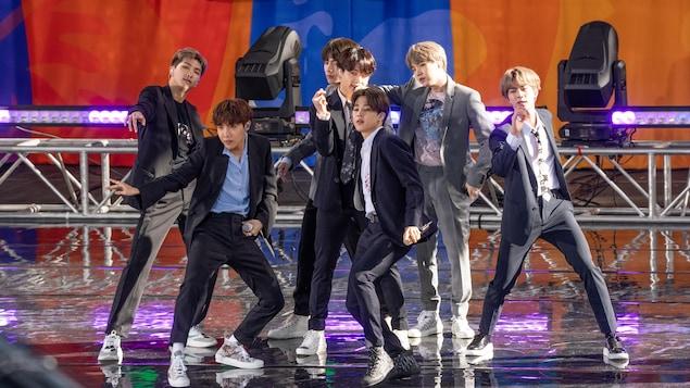 Les membres du groupe BTS dansent et chantent sur une scène.