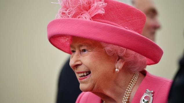La reine Élisabeth II, souriante, habillée tout en rose.