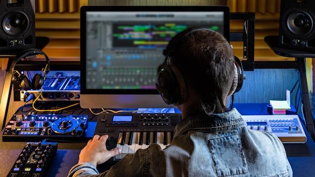 Un technicien de dos dans un studio d'enregistrement.