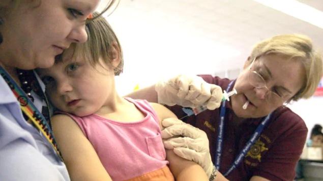 Une enfant se fait vacciner.