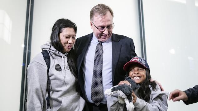 L'avocat Robert Tibbo avec à sa gauche Vanessa Rodel et à sa droite la jeune Keana, qui tient une peluche husky dans ses mains.