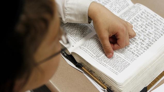 L'enfant est de dos et pose sa main sur le livre sacré pour mieux le lire.