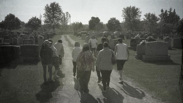 Anne Panasuk en compagnie d'Atimateks de Manawan, de dos, au cimetière de Joliette.