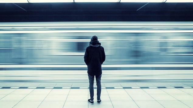 L'homme habillé chaudement est immobile. Il regarde passer le métro, flou.