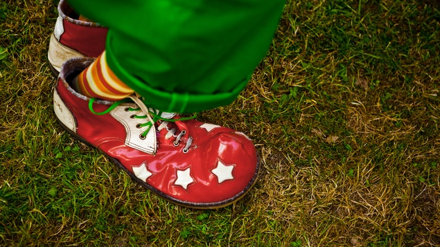 Une chaussure de clown, rouge avec des étoiles.