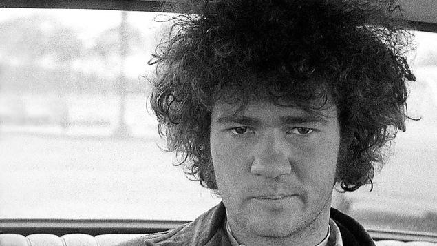 Robert Charlebois, jeune, assis dans une voiture, les cheveux ébouriffés.