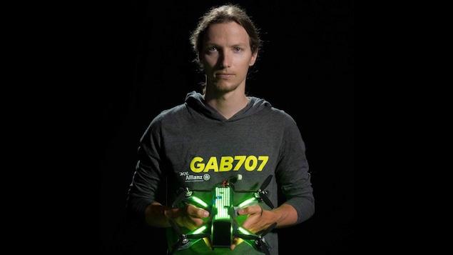 Une photo de Gabriel Kocher habillé d'un chandail gris à capuchon sur lequel est inscrit GAB707 en jaune. Il tient un drone à quatre hélices dans ses mains. Le dessus du drone est éclairé grâce à des dizaines de lumières LED vertes.