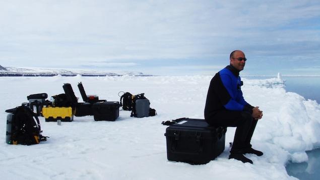 Mario Cyr assis sur une boîte d'équipement dans le Grand Nord.