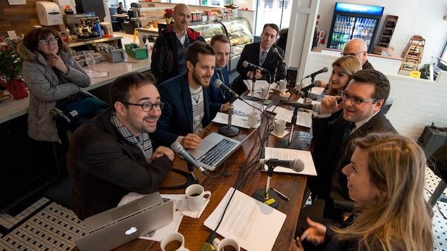Raphaël Bouvier-Auclair, Philippe-Vincent Foisy, Louis Blouin, Nick Gamache, Yves Malo, Madeleine Blais-Morin, Daniel Thibault et Fannie Olivier assis dans un café pour enregistrer l'émission.