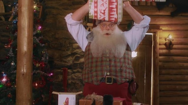 Nicolas Noël tient un gros cadeau sur sa tête.