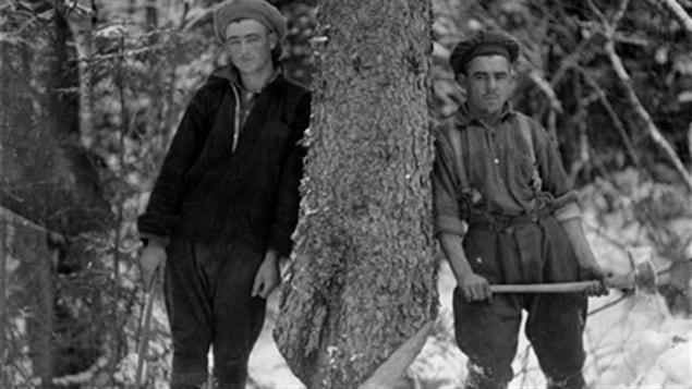 Deux bûcherons posent pour le photographe avant d'abattre un arbre. Circa 1925