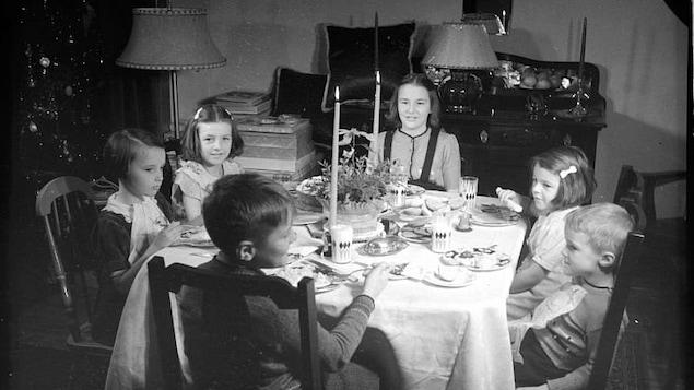 Un groupe d'enfants autour d'une table décorée de chandeliers, à l'occasion du temps des fêtes.