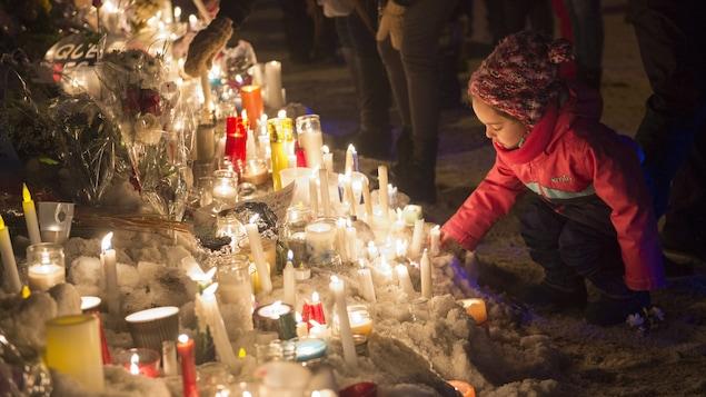 Une fillette allume une bougie en mémoire des victimes de la fusillade de Québec.
