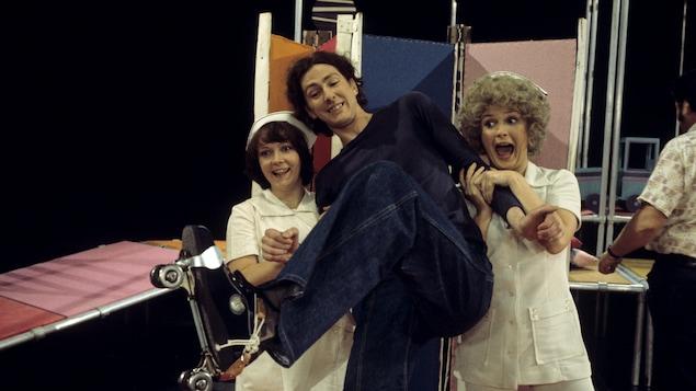 Dans un studio de télévision, les comédiennes Francine Ruel et Dorothée Berryman sont déguisées en infirmières et soutiennent le comédien Robert Gravel qui chausse des patins à roulettes.