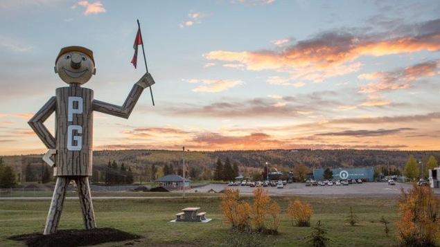 Une gigantesque figurine de bois avec les lettres P et G écrites sur lui tient un drapeau canadien.