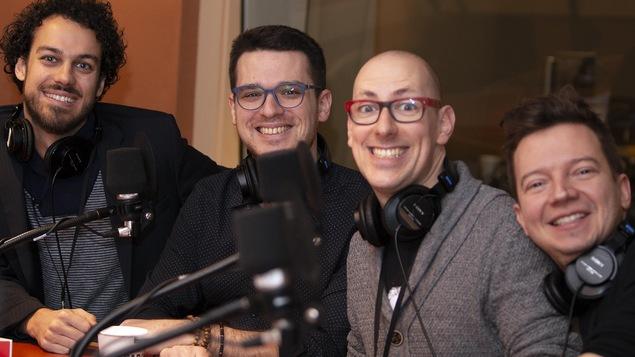 Quatre hommes sourient à la caméra.