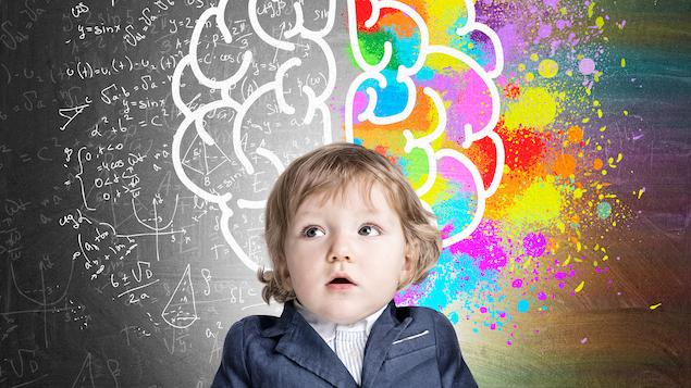 Portrait d'un adorable garçon portant un complet et posant devant un tableau sur lequel se dessinent des formules mathématiques et l'esquisse d'un cerveau en partie coloré en de multiples couleurs. Un concept illustrant l'intelligence et la créativité de l'enfant.