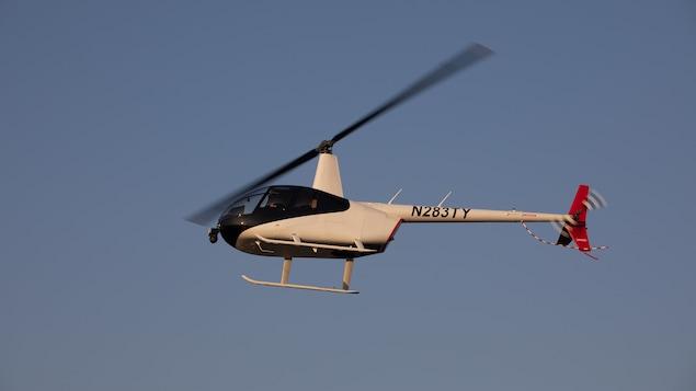 Un hélicoptère blanc vol dans les airs sous un ciel bleu.