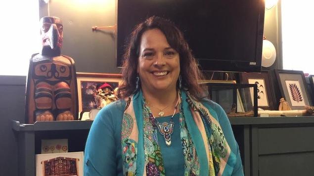 Une femme est  photographiée avec des oeuvres autochtones en arrière-plan.