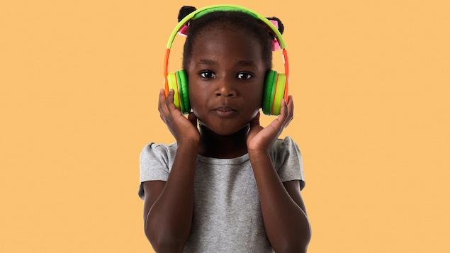Une petite fille tient des écouteurs sur ses oreilles.