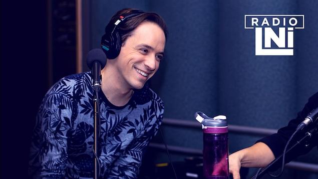 Photo de LeLouis Courchesne, souriant, devant un micro de radio.