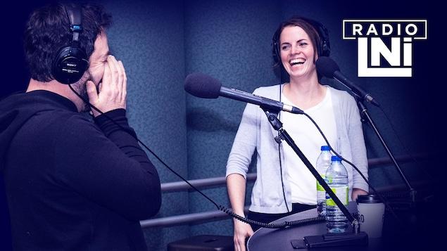Photo de Jeff Boudreault et Amélie Geoffroy dans un studio de radio, devant des micros, casques d'écoute sur la tête.