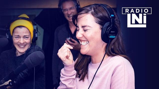 Photo de Sophie Cadieux et Florence Longpré en train de rire, dans un studio de radio, devant des micros et des casques d'écoute sur les oreilles.