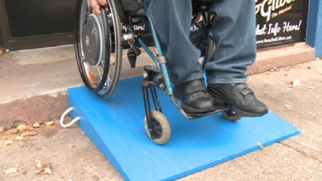 Une personnes en fauteuil roulant descend une rampe d'accès installée devant un magasin.