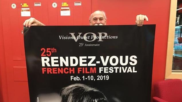 Un  homme se tient derrière une affiche qu'il tient et qui annonce les 25e Rendez-vous du cinéma québécois et francophone.