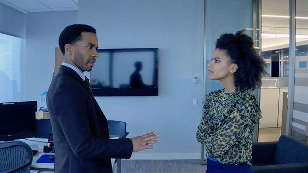 Dans un bureau, un homme discute avec une femme, sa main placée devant lui en signe d'opposition