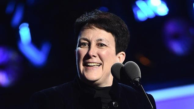 Au micro, tenant son prix entre les mains, Jennifer Higdon sourit, sa tête tournée vers la gauche. Elle est vêtue de noir et se détache d'un décor bleuté.