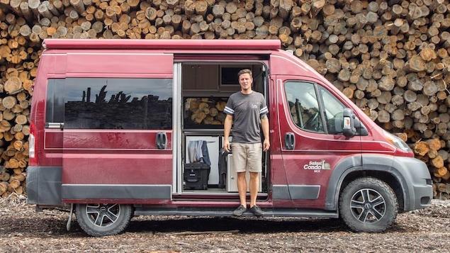 Le voyageur pose devant sa camionnette rouge, stationnée aux abords d'une immense corde de bois