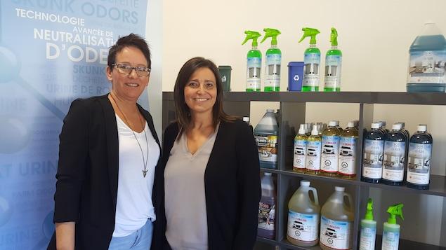 La propriétaire de SOS Odeurs, Josée Samson (à droite) en compagnie de son adjointe administrative Nathalie Grenier. Elles sont devant une étagère remplie de bouteilles de produits neutralisants les odeurs.