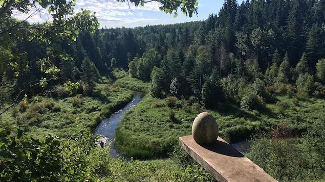 Une sculpture en forme d'oeuf surplombant un ruisseau dans la forêt boréale.