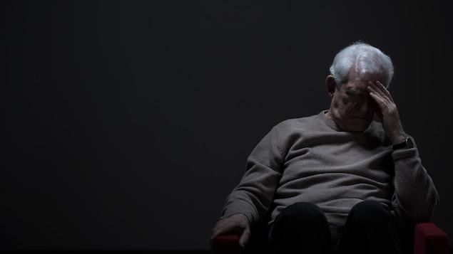 Un homme qui déprime devant un mur gris.