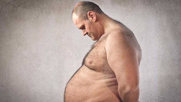 Un homme triste observe son ventre.