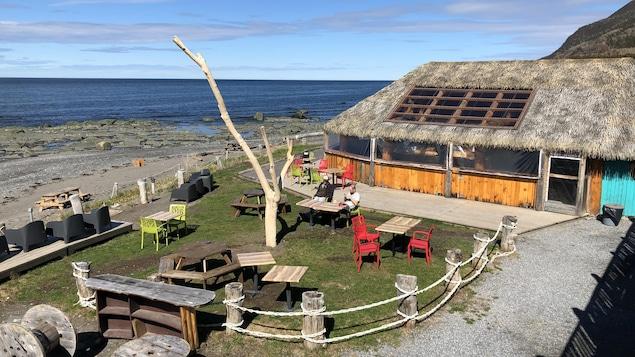 On voit la terrasse du Sea Shack, avec le bar couvert de paille, avec le fleuve en arrière-plan.