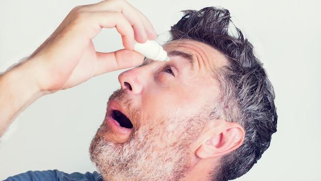 Un homme utilisant des gouttes pour les yeux.