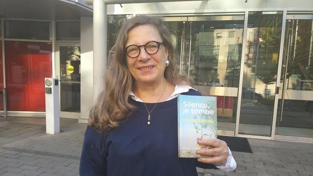 Une femme se tient debout avec son livre qu'elle tient dans sa main. Elle est à l'extérieur, devant la porte d'entrée de Radio-Canada.