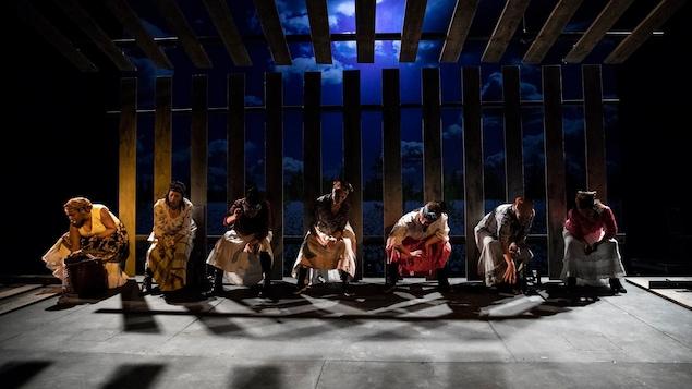 Des femmes sur une scène avec des costumes d'époque sont assises devant une palissade.