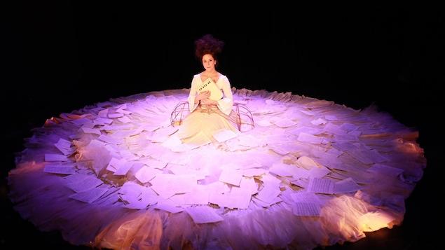 La comédienne Sofi Lambert, assise à genoux sur scène, tient un petit instrument de musique contre sa poitrine. Elle porte une immense robe sur laquelle il y a plusieurs feuilles de papier.