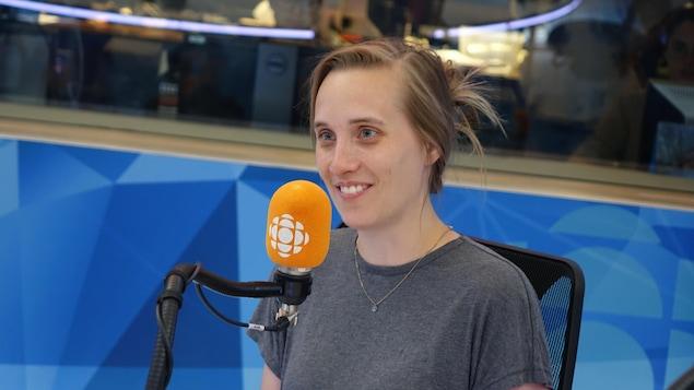 Une femme avec les cheveux attachés portant un chandail gris regarde vers la gauche en souriant les yeux brillants.